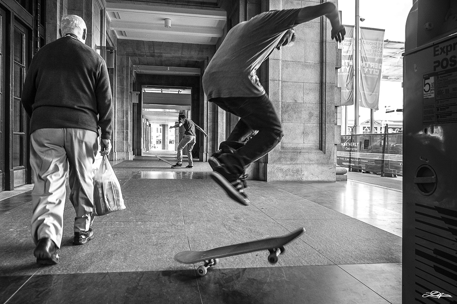 A skateboarder performing a trick as an old gentleman walks past in the City of Perth